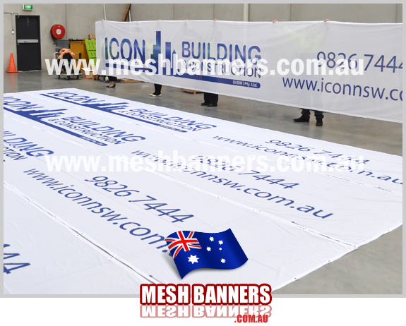 Icon People holding up 10 metre construction mesh section of banner = 50m