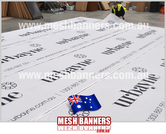 Woman checking the new Urbayne temporary fencing banner signs. Each temporary fence banner sign is used as builders dust and privacy screening during the construction of new homes and renovations around melbourne australia. We supply cheap banner signs melbourne and australia wide including temporary fencing banner signs and mesh banners for building