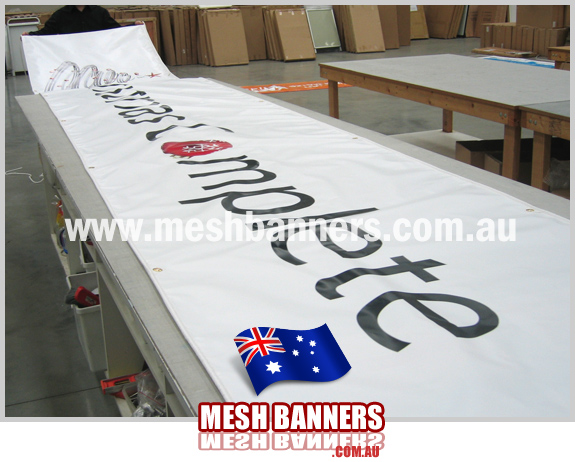 Person rolling out a long banner sign on the workbench